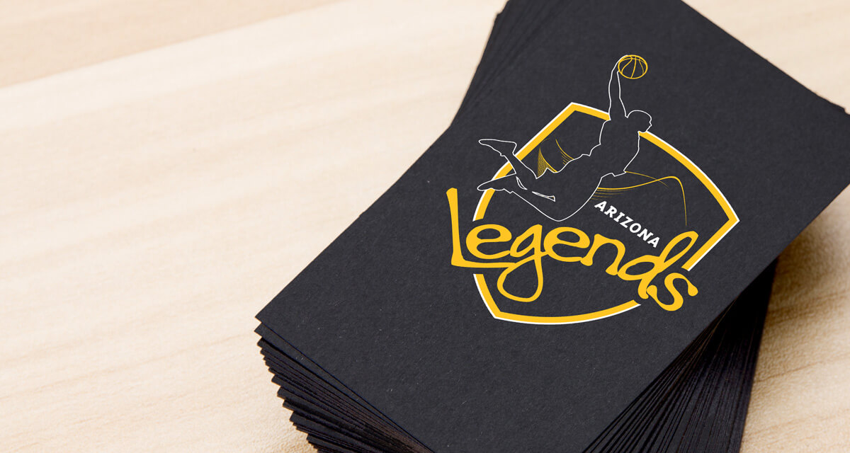 Sports team logo design emblazoned on a stack of party napkins featuring basketball player silhouette dunking over a black and gold shield.