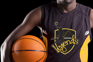 A player holds a basketball between his elbow and hip to pose for a photo featuring a FabCom-designed sports team logo.
