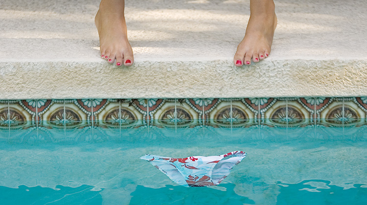 Close up image showing design detail of a print ad created by FabCom for a Contractor Management company featuring women feet and bikini bottoms floating in a pool.